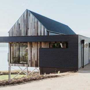 Пример оригинального дизайна: одноэтажный, разноцветный частный загородный дом в современном стиле с комбинированной облицовкой, двускатной крышей и металлической крышей