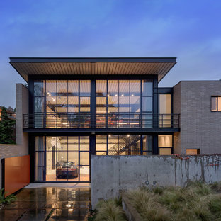 Inspiration for an industrial gray two-story glass exterior home remodel in Seattle
