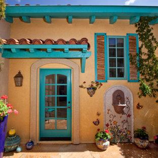 Cette image montre une façade de maison beige sud-ouest américain de taille moyenne et de plain-pied avec un revêtement en adobe.