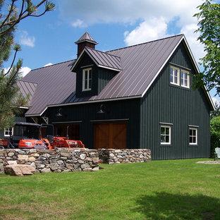 Lantlig inredning av ett svart trähus, med två våningar, sadeltak och tak i metall