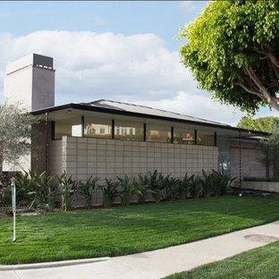 Inspiration for a 1950s gray one-story concrete house exterior remodel in Los Angeles with a hip roof and a metal roof