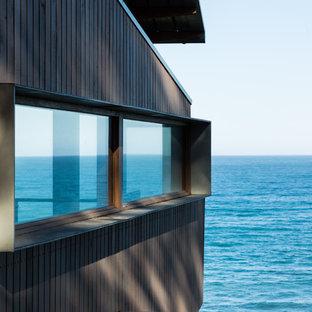 Imagen de fachada de casa gris, marinera, de tamaño medio, a niveles, con revestimiento de madera, tejado a dos aguas y tejado de metal