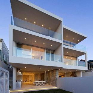 Esempio della facciata di una casa bifamiliare beige contemporanea a tre piani con tetto piano