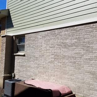 Ejemplo de fachada gris, tradicional, de tamaño medio, de dos plantas, con revestimiento de ladrillo y tejado a dos aguas