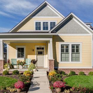 Idee per la facciata di una casa unifamiliare gialla american style a un piano di medie dimensioni con rivestimento in legno, tetto a capanna e copertura a scandole
