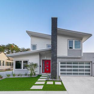 Imagen de fachada de casa gris, actual, de tamaño medio, de dos plantas, con revestimiento de aglomerado de cemento, tejado de un solo tendido y tejado de metal
