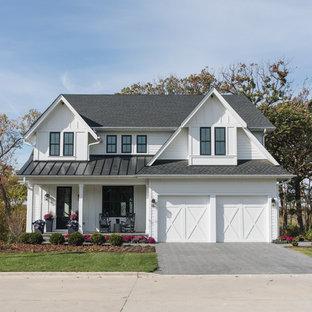 Ispirazione per la facciata di una casa unifamiliare bianca country a due piani con rivestimento in vinile, tetto a capanna e copertura mista