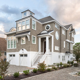 Coastal beige three-story wood exterior home photo in Other with a hip roof and a shingle roof