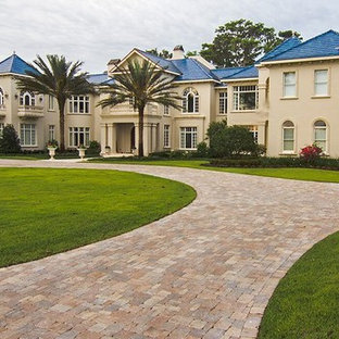 This is an example of an expansive mediterranean two-storey stucco beige exterior in Tampa with a hip roof.