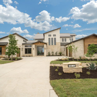 Inspiration for a large contemporary beige two-story stone house exterior remodel in Austin with a metal roof