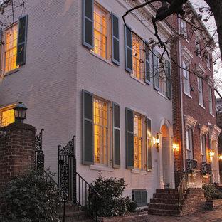 Aménagement d'une façade de maison blanche classique de taille moyenne et à un étage.