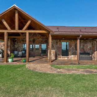 Mid-sized mountain style brown one-story stone exterior home photo in Austin with a metal roof
