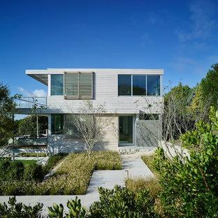 Ispirazione per la facciata di una casa unifamiliare beige stile marinaro a due piani con rivestimenti misti e tetto piano