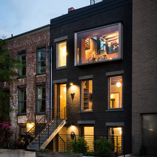 Example of an urban black three-story brick exterior home design in New York with a shingle roof