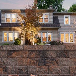 Diseño de fachada de casa beige, clásica, de dos plantas, con revestimiento de aglomerado de cemento, tejado a doble faldón y tejado de teja de madera