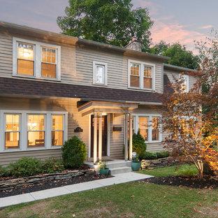 Ejemplo de fachada de casa beige, clásica, de dos plantas, con revestimiento de aglomerado de cemento, tejado a doble faldón y tejado de teja de madera