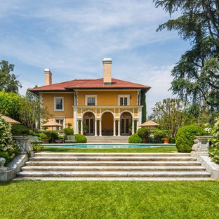 Inspiration for a mediterranean yellow two-story house exterior remodel in Los Angeles with a hip roof