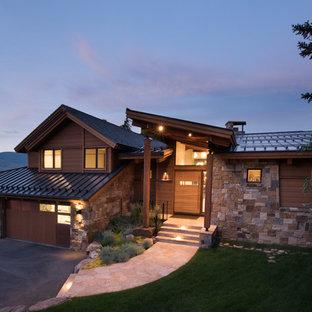 Ejemplo de fachada de casa marrón, contemporánea, extra grande, de tres plantas, con revestimiento de piedra, tejado de un solo tendido y tejado de metal