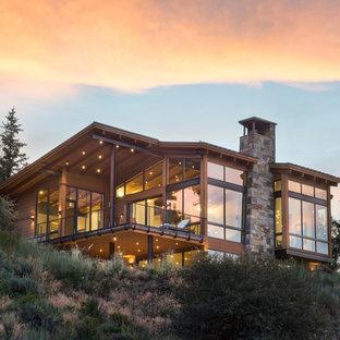 Inspiration för ett mycket stort funkis brunt hus, med tre eller fler plan, pulpettak och tak i metall