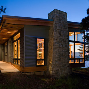 На фото: маленький, двухэтажный дом в стиле модернизм с облицовкой из металла для охотников с