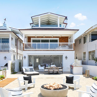 Example of a coastal three-story wood exterior home design in Orange County