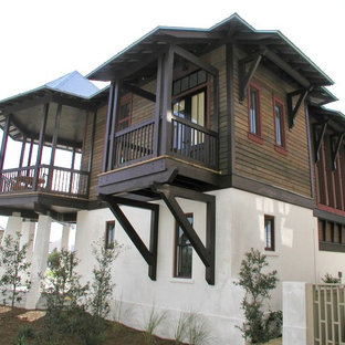 Example of a mid-sized island style multicolored two-story wood house exterior design with a hip roof and a metal roof