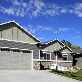 Réalisation d'une façade de maison double grise craftsman de taille moyenne et de plain-pied avec un revêtement en panneau de béton fibré, un toit à quatre pans et un toit en shingle.