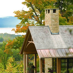 Rustic one-story stone gable roof idea in Burlington with a mixed material roof