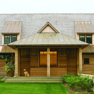This is an example of a medium sized rustic two floor exterior in Burlington with wood cladding and a mixed material roof.