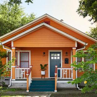 Стильный дизайн: одноэтажный, деревянный, оранжевый частный загородный дом среднего размера в стиле фьюжн с двускатной крышей - последний тренд