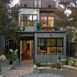Foto de fachada ecléctica, de tamaño medio, de tres plantas, con revestimiento de hormigón y tejado a dos aguas