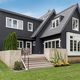 Réalisation d'une façade de maison noire nordique de taille moyenne et à un étage avec un revêtement en panneau de béton fibré et un toit à deux pans.