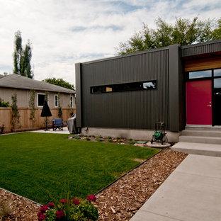 Ejemplo de fachada negra, moderna, de tamaño medio, de una planta, con revestimiento de metal y tejado plano