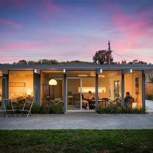 サンフランシスコの中くらいのミッドセンチュリースタイルのおしゃれな家の外観 (ガラスサイディング、グレーの外壁) の写真