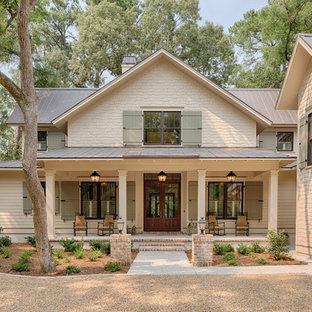 Esempio della facciata di una casa beige country a due piani di medie dimensioni con rivestimento in legno e tetto a capanna