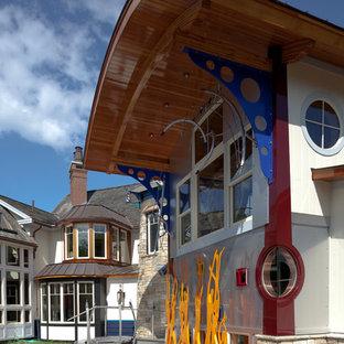 Imagen de fachada de casa blanca, ecléctica, de tamaño medio, de dos plantas, con revestimientos combinados, tejado de un solo tendido y tejado de varios materiales