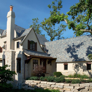 Large elegant beige two-story stone gable roof photo in Chicago