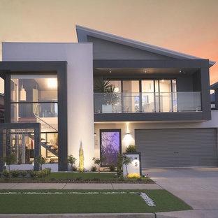Foto på ett stort funkis vitt hus, med två våningar och platt tak