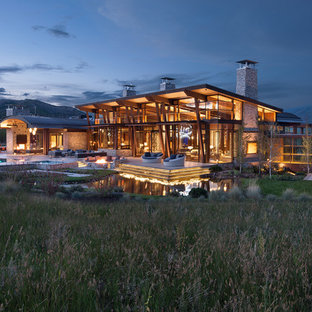Inspiration for a rustic brown two-story glass house exterior remodel in Denver with a shed roof and a metal roof