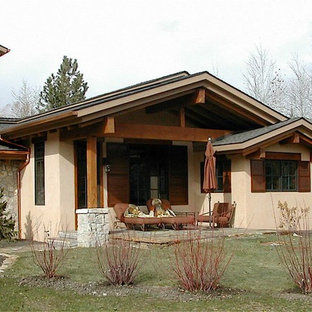 Mid-sized tuscan beige two-story mixed siding exterior home photo in Other with a clipped gable roof