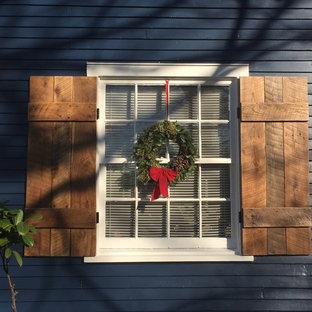ナッシュビルのシャビーシック調のおしゃれな家の外観 (木材サイディング、青い外壁、寄棟屋根) の写真