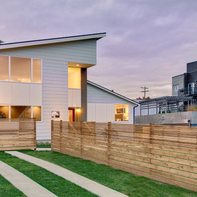 Example of a trendy white two-story exterior home design in Seattle with a shed roof