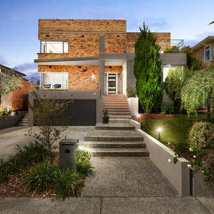 This is an example of a contemporary brick red house exterior in Melbourne with a flat roof.