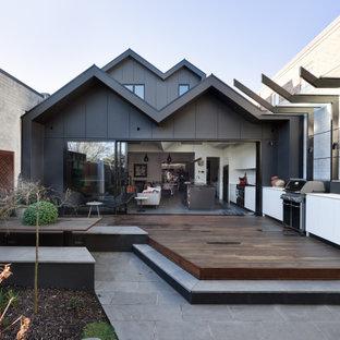 Inredning av ett modernt mellanstort svart hus, med två våningar, metallfasad, sadeltak och tak i metall