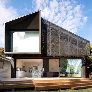 Пример оригинального дизайна: серый частный загородный дом среднего размера в современном стиле с разными уровнями, облицовкой из металла, двускатной крышей и металлической крышей