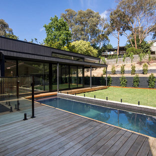 This is an example of a contemporary one-storey black house exterior in Melbourne with wood siding and a flat roof.