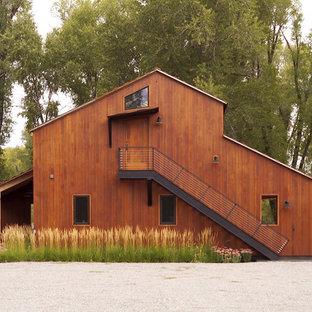 Ispirazione per la facciata di una casa unifamiliare grande marrone rustica a due piani con rivestimenti misti e copertura in metallo o lamiera