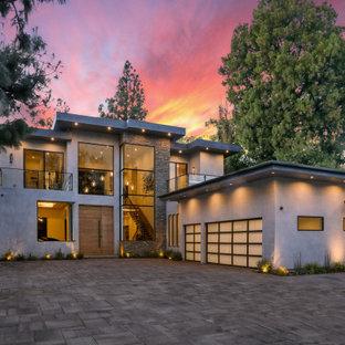 Пример оригинального дизайна: большой, двухэтажный, серый частный загородный дом в современном стиле с плоской крышей и комбинированной облицовкой