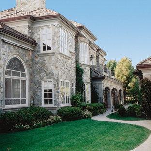 Modelo de fachada gris, mediterránea, grande, de dos plantas, con revestimiento de piedra y tejado a dos aguas