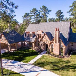 ヒューストンのトラディショナルスタイルのおしゃれな家の外観 (石材サイディング、ベージュの外壁、切妻屋根、板屋根) の写真